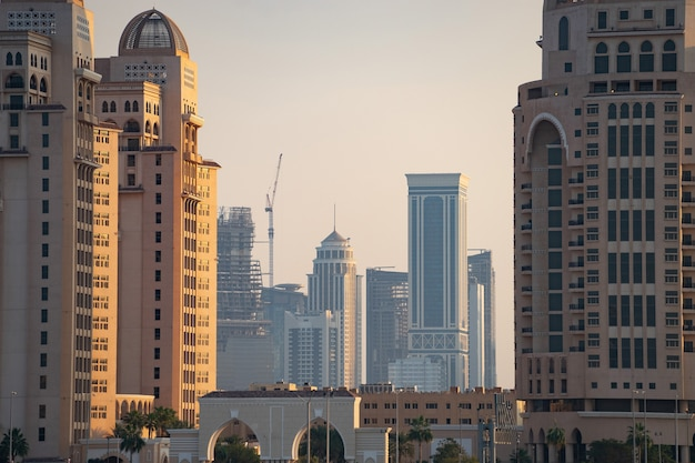 Doha, katar, pejzaż nowoczesnych, ale wciąż oldschoolowych budynków podczas zachodu słońca.