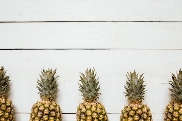 Dojrzała ananas granicy rama na białym drewnianym tle. koncepcja kreatywna owoców tropikalnych. pokój dla kopii, tekstu, liternictwa.
