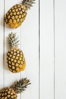 Dojrzała Ananas Granicy Rama Na Białym Drewnianym Tle. Koncepcja Kreatywna Owoców Tropikalnych. Pokój Dla Kopii, Tekstu, Liternictwa. Premium Zdjęcia