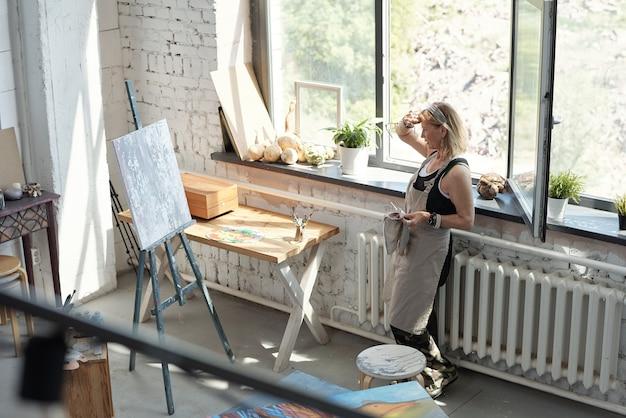 Dojrzała artystka w fartuchu zmęczona po malowaniu ocierając pot z czoła i patrząc na abstrakcyjny obraz