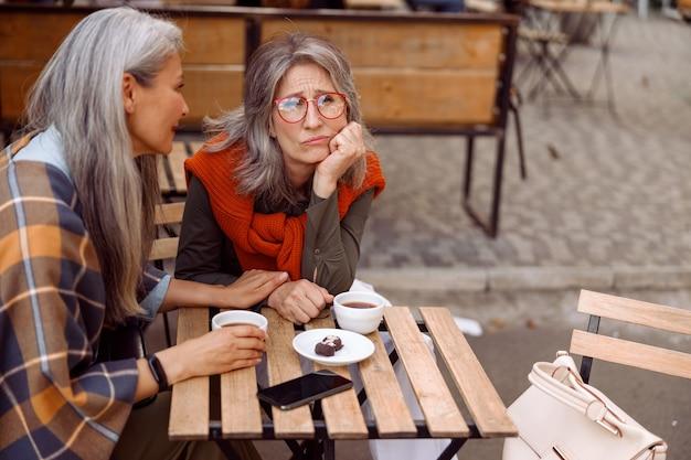 Dojrzała azjatycka dama rozwesela zdenerwowanego siedzącego razem przy małym stoliku w ulicznej kawiarni
