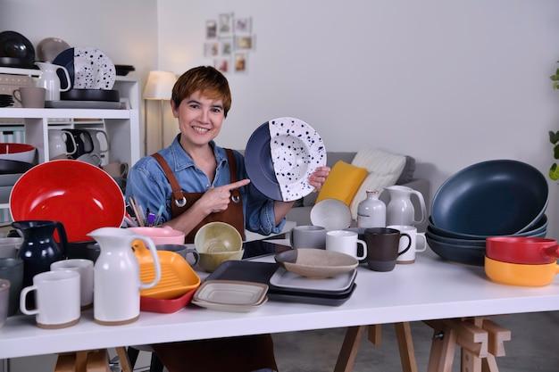 Dojrzała azjatycka kobieta przedsiębiorca / właścicielka firmy pokazująca swój gliniany produkt ceramiczny i pracująca w domu