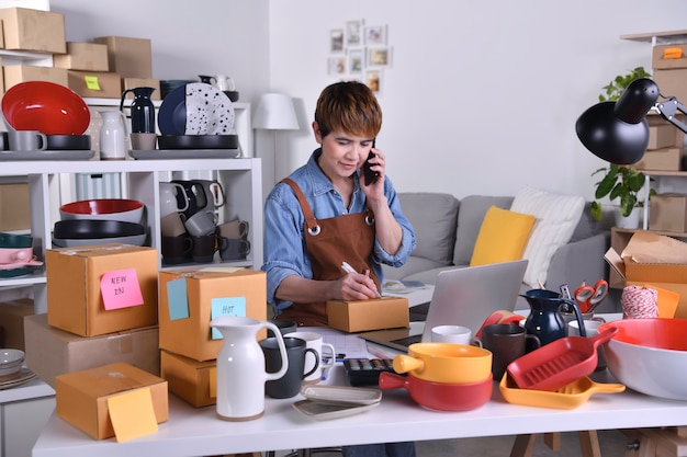 Dojrzała azjatycka kobieta przedsiębiorca, właścicielka firmy pracująca w domowym biurze, potwierdzająca zamówienia od klienta przez telefon. właściciel sklepu internetowego przyjmujący zamówienie przez telefon