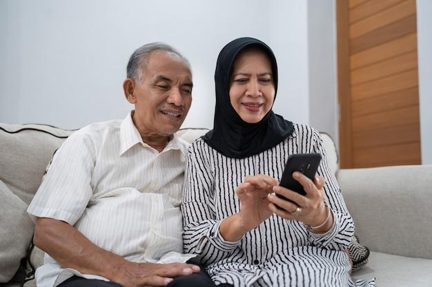 Dojrzała azjatykcia para używa smartphone