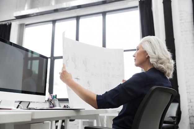Dojrzała biznesowa kobieta analizuje mapę trzymającą przed nią