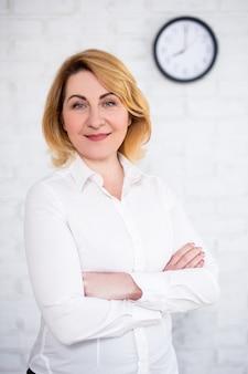Dojrzała biznesowa kobieta pozuje nad białym ceglanym murem z biurowym zegarem