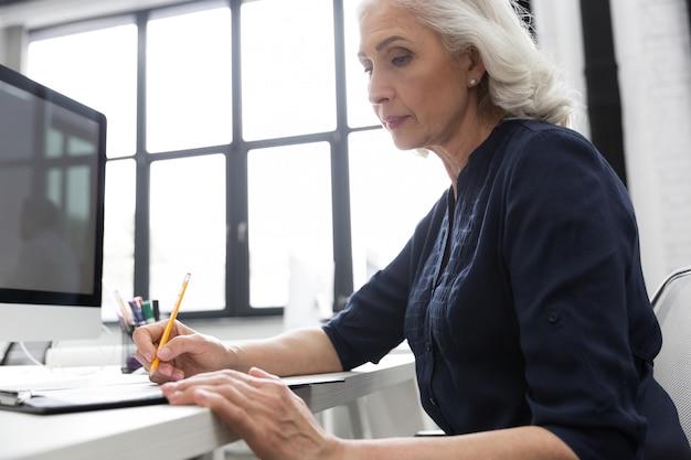 Dojrzała biznesowa kobieta robi notatkom na kawałku papieru
