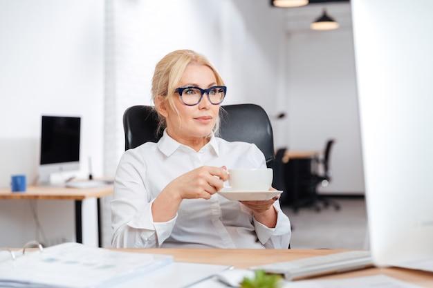 Dojrzała bizneswoman pije kawę z komputerem pc w biurze