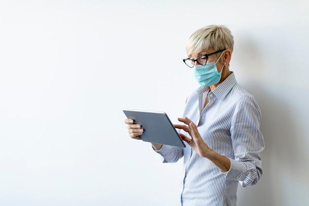 Dojrzała bizneswoman używa ręcznego cyfrowego tabletu i nosi maskę, aby zapobiec infekcji koronawirusem