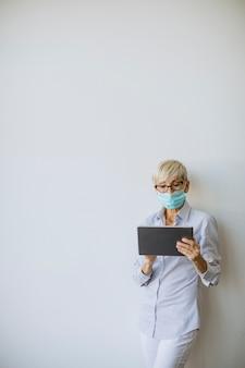 Dojrzała bizneswoman używa ręcznego cyfrowego tabletu i nosi maskę, aby zapobiec infekcji wirusem koronowym