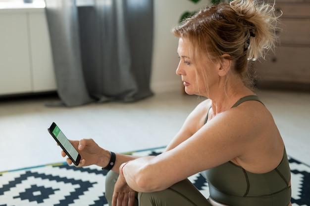 Dojrzała blond kobieta w sportowym garniturze siedzi na dywanie w salonie i przewija w smartfonie podczas ćwiczeń online lub kursów fitness