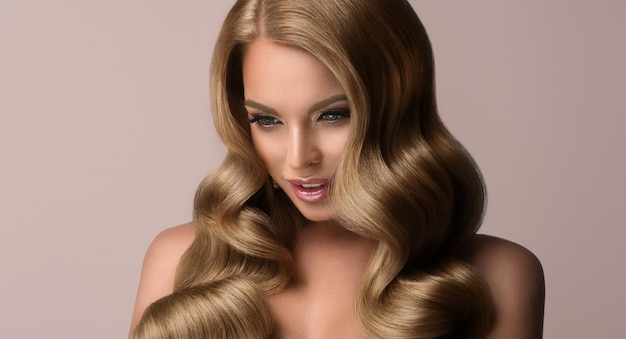 Dojrzała blond kobieta z obszernymi lokami, doskonałymi falującymi włosami, piękny model o długich, gęstych, kędzierzawych włosach i delikatnym makijażu z różową szminką. sztuka fryzjerska, pielęgnacja włosów i makijaż.