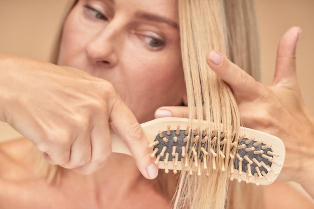 Dojrzała blondynka czesanie włosów selektywne skupienie