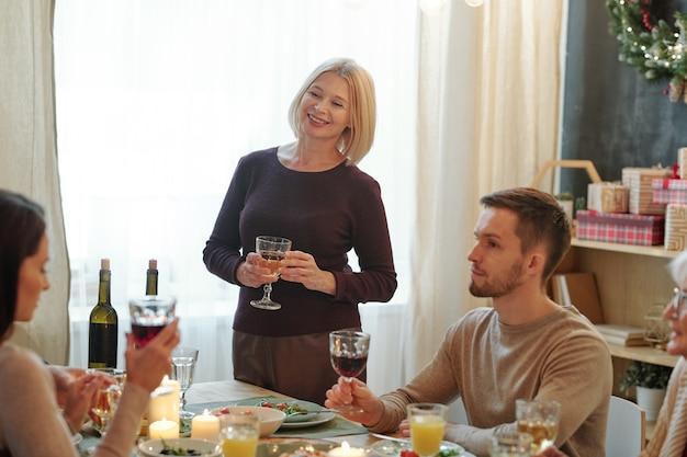 Dojrzała blondynka opiekuje się kieliszkiem wina przy stole, patrząc na rodzinę podczas uroczystej kolacji w domu