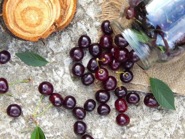 Dojrzała bordowa wiśnia wysypuje się ze szklanego słoika na płótno