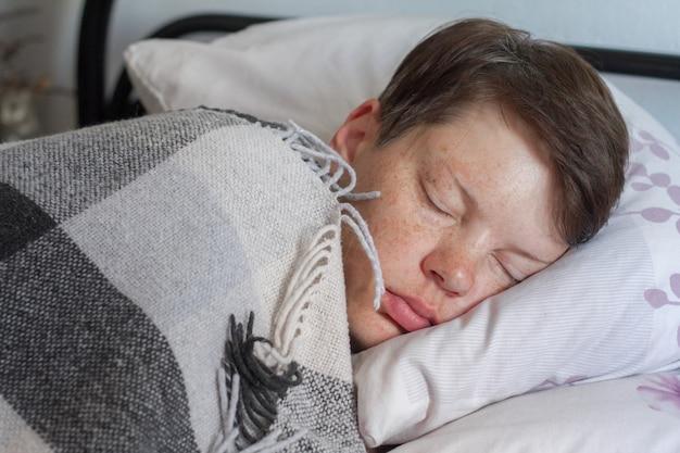 Dojrzała brunetka kobieta śpi w łóżku pod kocem w kratę, pojęcie choroby lub przeziębienia, leczenie w domu