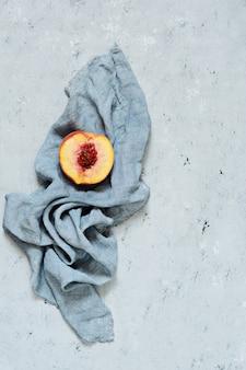 Dojrzała brzoskwinia na szarym (niebieskim) tle. soczyste letnie owoce, miejsce na kopię.