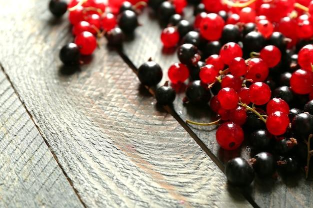 Dojrzała czerwona i czarna porzeczka na drewnianym tle