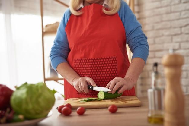 Dojrzała dama kroi warzywa w kuchni nożem.