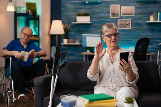 Dojrzała emerytowana para na nowoczesnej rozmowie wideo w domu