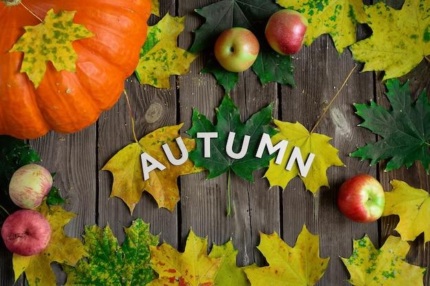 Dojrzała jesienna dynia z liśćmi i jabłkami na drewnianym stole