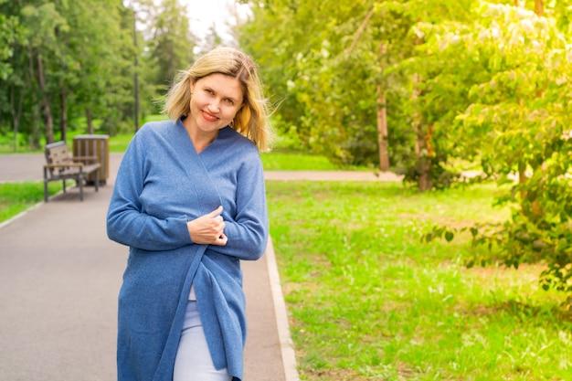Dojrzała kaukaska kobieta uśmiechając się i owijając się w sweter podczas spaceru po parku. blondynka uśmiecha się spacerując ścieżką wśród drzew w słoneczną, ale chłodną pogodę