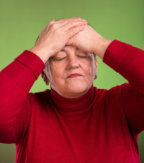 Dojrzała kobieta cierpi na bóle głowy na zielonym tle