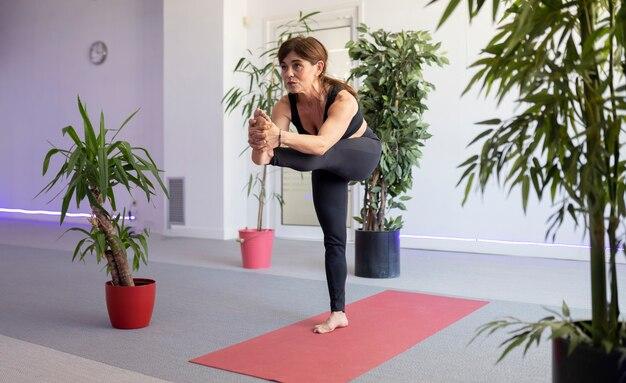 Dojrzała kobieta ćwiczy jogę na siłowni