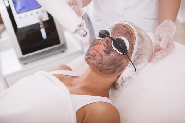 Dojrzała kobieta dostaje twarzowego skincare traktowanie przy salonem piękności