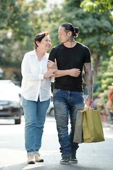 Dojrzała kobieta i jej dorosły syn spacerują po ulicy po zakupach, niosą papierowe torby i rozmawiają o nowościach