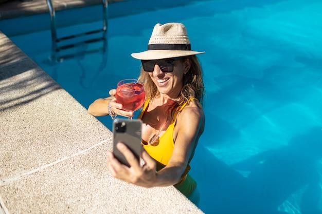 Dojrzała kobieta kaukaski co autoportret do basenu z telefonem komórkowym. ma na sobie kapelusz, okulary przeciwsłoneczne i żółty strój kąpielowy. ona trzyma czerwony koktajl w filiżance. ona się uśmiecha
