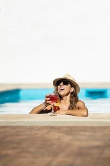 Dojrzała kobieta kaukaski pije koktajl do basenu. ma na sobie kapelusz, okulary przeciwsłoneczne i żółty strój kąpielowy. ona pije czerwony koktajl w filiżance. ona się uśmiecha