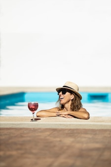 Dojrzała kobieta kaukaski śmieje się do basenu. ma na sobie kapelusz, okulary przeciwsłoneczne i żółty strój kąpielowy. jest wspierana przy basenie.