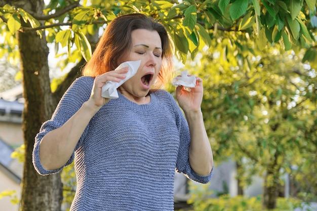 Dojrzała kobieta kicha w chusteczce