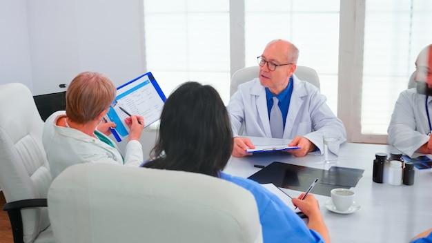Dojrzała kobieta lekarz wskazując w schowku podczas odprawy ze współpracownikami pracującymi w sali konferencyjnej szpitala. ekspert kliniczny terapeuta rozmawiający z kolegami o chorobie, specjalista od medycyny
