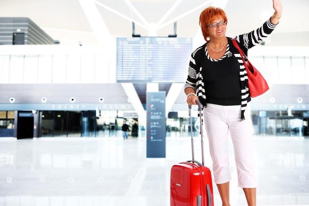 Dojrzała kobieta machająca na pożegnanie na lotnisku