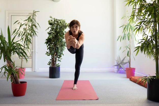 Dojrzała kobieta na siłowni robi rozciąganie