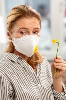 Dojrzała kobieta o blond włosach ubrana w pasiastą koszulę z alergią na kwiat kwiatów