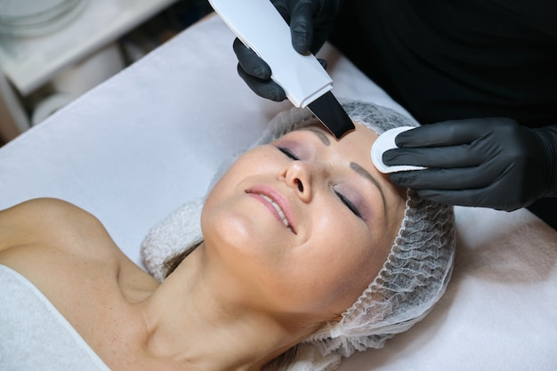Dojrzała kobieta otrzymywa oczyszczanie twarzy w salonie piękności