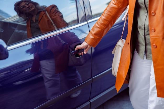 Dojrzała kobieta otwiera drzwi fioletowego samochodu stojącego na zbliżenie ulicy miasta