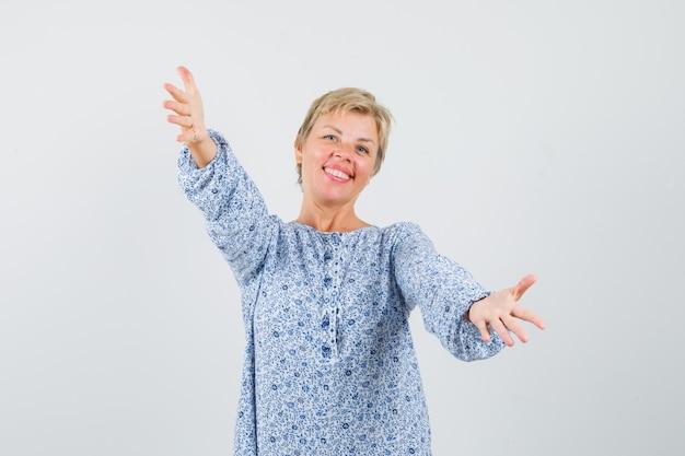 Dojrzała kobieta otwierająca ramiona do przytulenia w koszuli i wyglądająca na szczęśliwą.
