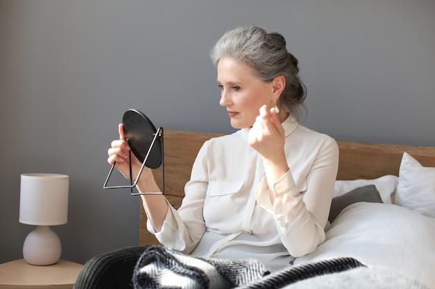 Dojrzała kobieta, patrząc w lustro i dotykając twarzy w domu.