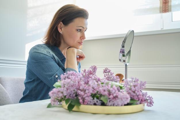 Dojrzała kobieta patrzeje jej twarz w lustrze