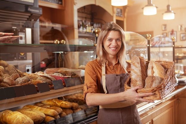 Dojrzała kobieta piekarz pracuje w swoim sklepie piekarniczym