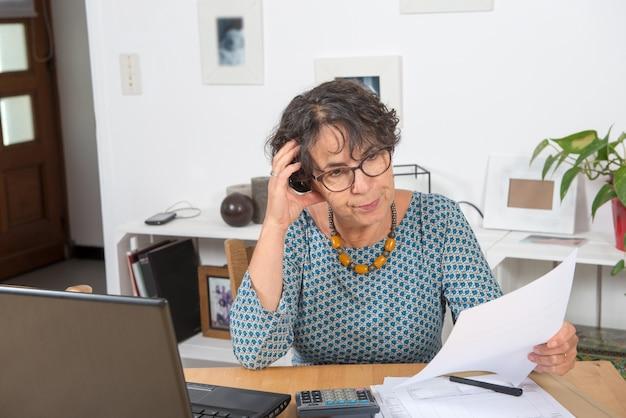 Dojrzała kobieta płaci rachunki z laptopem w domu