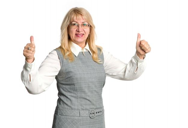 Dojrzała kobieta pokazuje aprobaty, odizolowywać na białym tle. sukces, starsza kobieta nauczyciel.