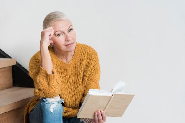 Dojrzała kobieta pozuje na schodkach podczas gdy trzymający książkę