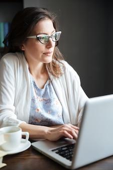 Dojrzała kobieta pracuje na laptopie i ma filiżankę herbata