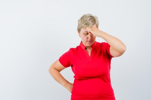 Dojrzała kobieta przeciera oczy i nos w czerwonej koszulce i patrzy zamyślona.