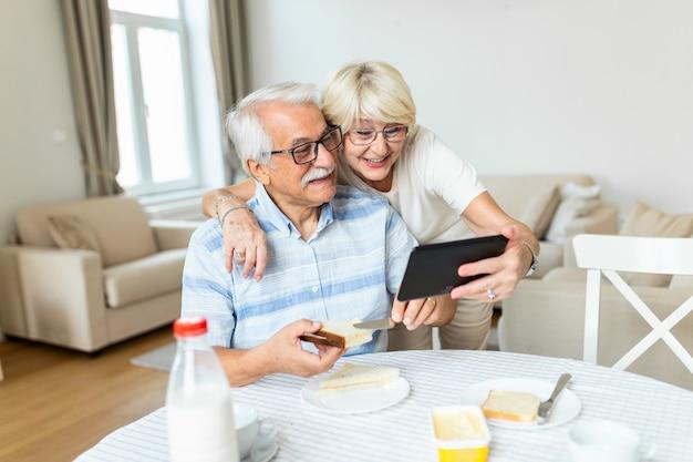 Dojrzała kobieta przytula męża i prowadzi rozmowę wideo z wnukami